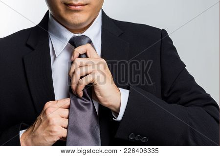 Young Happy Businessman With Black Suit Adjusting His Necktie Isolated On White Background