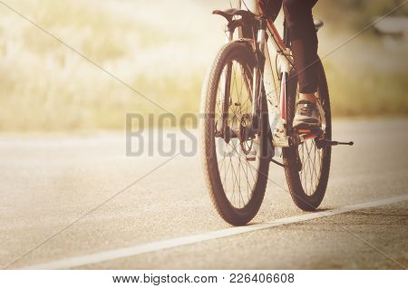 Young Asian Woman Riding A Bicycle On Bike Way In The Public Park,relaxing,exercise Concept.