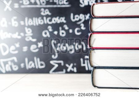 Stack And Pile Of Books In Front Of A Blackboard In School. Math Equation Handwritten On Chalkboard.