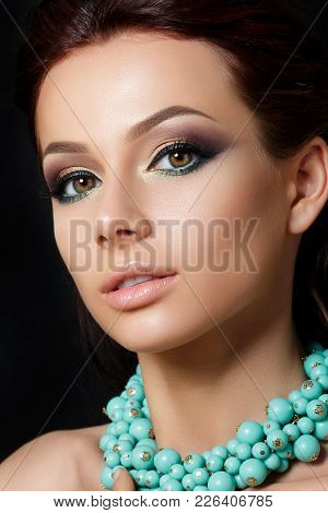 Portrait Of Young Beautiful Woman With Evening Make Up Wearing Blue Necklace. Model Posing Over Dark
