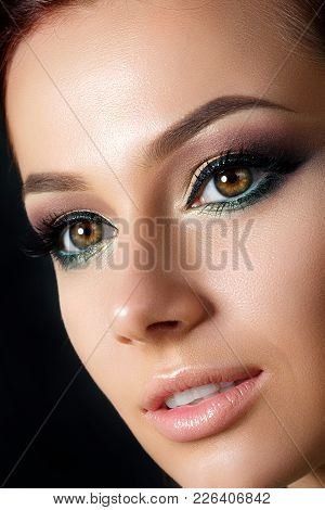 Closeup Portrait Of Young Beautiful Woman With Evening Make Up. Model Posing Over Dark Background. S