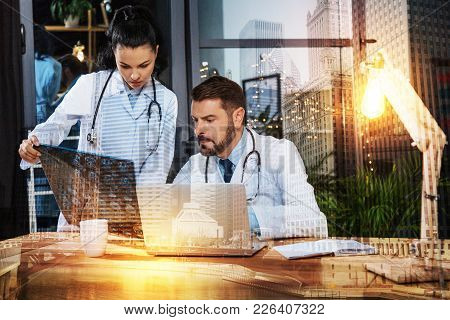 Consulting Specialist. Calm Experienced Qualified Doctors Frowning And Looking Concentrated While Si