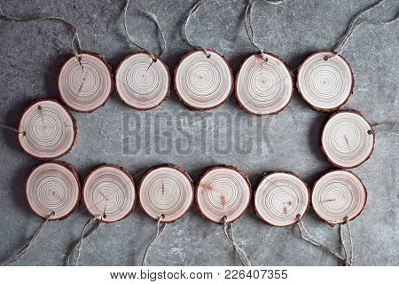 Natural wood handmade medals with linen twine. Stack of wooden homemade medals on grey grunge table. Round wood slices background. Wood banch cross section texture. Space for text. poster