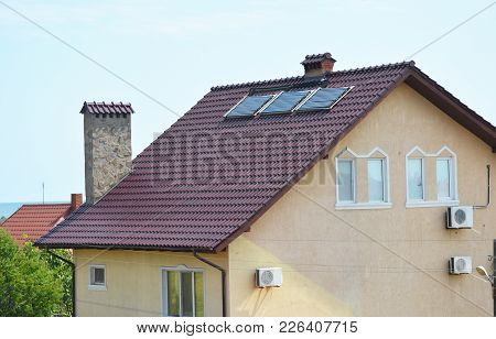 Modern Cottage Roof With Solar Water Heater Panels And Air Conditioner Compressors For Energy Effici