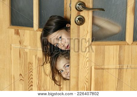 Children Look Out Of The Door To The Room Of The Parents
