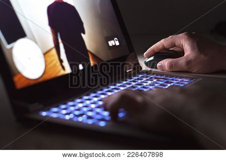 Young Man Playing Video Game With Laptop. Gamer With Computer In Dark Or Late At Night. Hands On Mou