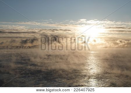 Cloudy Sunrise Over Mountainous Seacoast With Water Evaporation Over It.