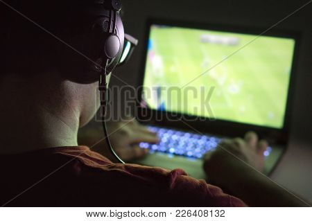 Playing Video Games With Laptop. Young Man Plays Online Soccer Or Football On Computer. Back View Of