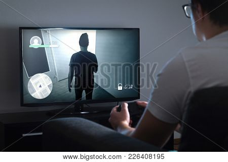 Young man playing video game at home with console. Gamer with controller or gamepad in hand. TV with action game on screen. Late at night or in dark. poster