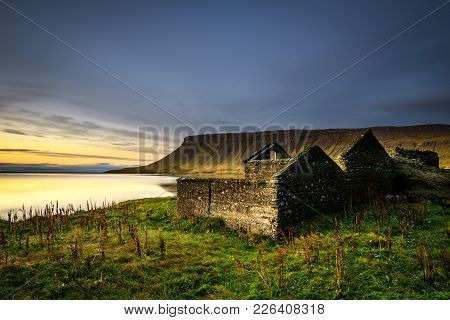 Scenic Landscape Including Ruined House, Typical Cliffs And A Lake In Iceland. Long Exposure.