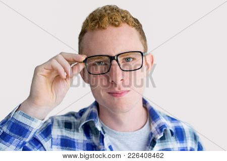 Closeup Of Contend Red Haired Young Caucasian Man Adjusting Glasses. Positive Student Advertising Gl