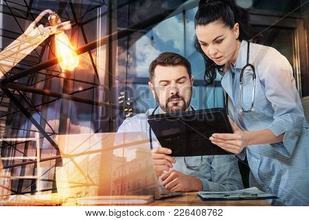 Convenient Device. Clever Responsible Young Doctor Showing Important Information On The Screen Of A