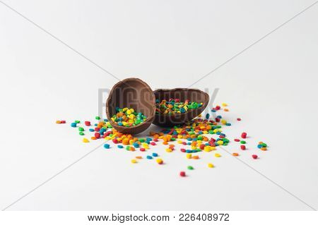 Broken Chocolate Easter Egg Into Two Halves With A Colorful Candy Decorations On A White Background.