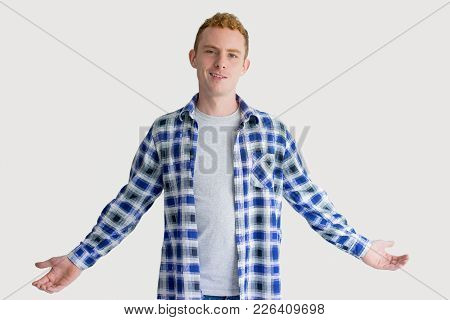 Grinning Red Haired Caucasian Man Spreading Hands In Helpless Gesture. Portrait Of Young Freelancer