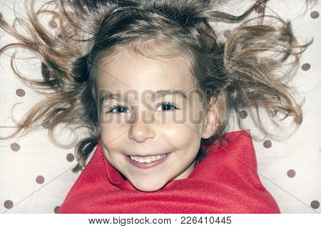 A Truly Beautiful Little Girl With Shaggy Hair On The Pillow In Red Plaid