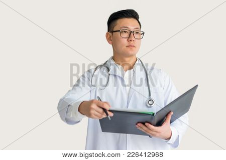 Serious Young Asian Male Practitioner Wearing Glasses Holding Pen And Clipboard. Resident Reviewing
