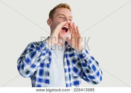Smiling Red Haired Caucasian Guy Shouting Loud With Hands At Mouth. Young Man Announcing Important G