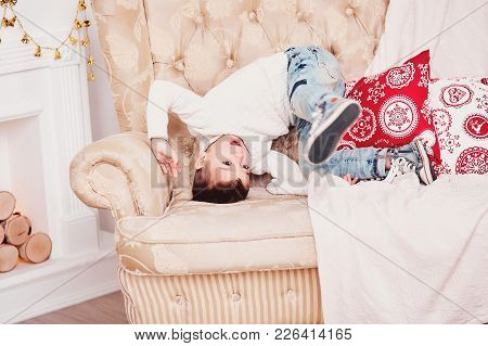 A Cute Boy Is Tumbling On The Couch. A Sporty Guy In A White Knitted Sweater And Jeans And A Stylish