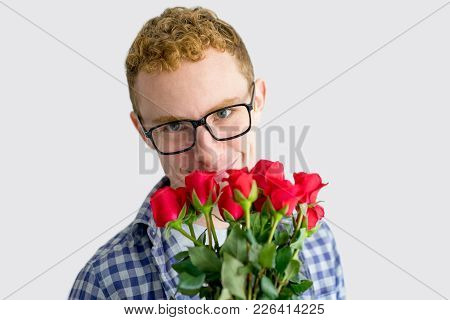 Smiling Red Haired Caucasian Guy With Bunch Of Red Roses. Shy Young Man Posing With Flowers For Spec