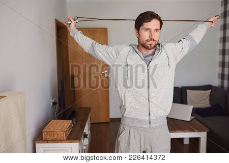 Fit Young Man In Sportswear Exercising With A Skipping Rope While Working Out Alone In His Apartment