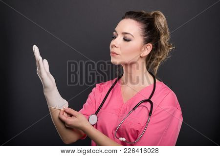 Portrait Of Beautiful Young Doctor Putting On Sterile Gloves