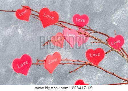 Red Hearts With An Inscription Love Hang On Branches On A Gray Concrete Background. Love Tree. The C