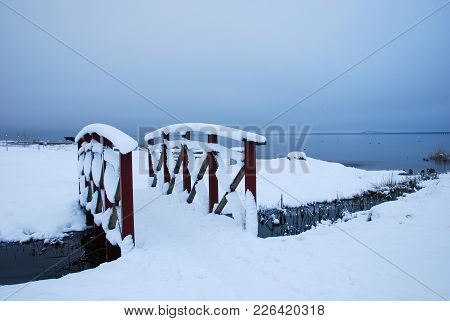 Snowy Wooden Footbridge Across A Small Creek By The Coast Of The Baltic Sea On The Swedish Island Ol