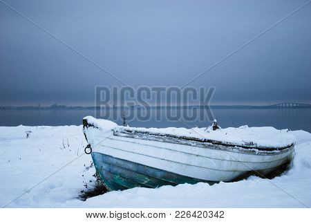 Winter Paused Old Wooden Rowboat By The Coast Of The Swedish Island Oland In The Baltic Sea
