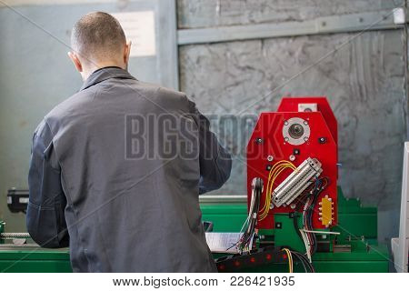 Electrician Works With Parts Of Energy Equipment On Plant, Rear View