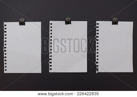 Three White New Empty Notepad Sheets With Black Metallic Paperclips On The Top Laying On Black Backg