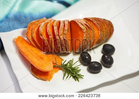 Homemade Orange Sweet Potato With Olives And Rosemary. Hassel Back Potato.