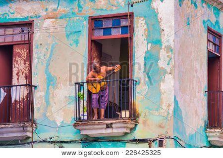 HAVANA, CUBA - DEC 4, 2015: Urban scene with musician in the balcony of old colonial building in Old Havana, Cuba