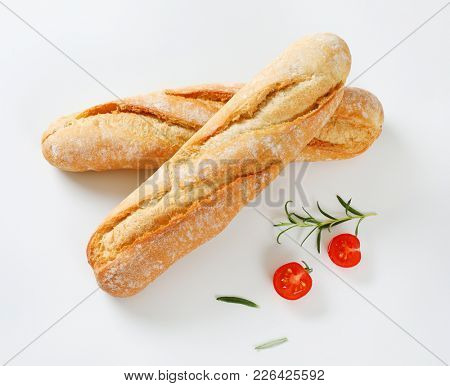 short French baguettes, rosemary and cherry tomato on white background
