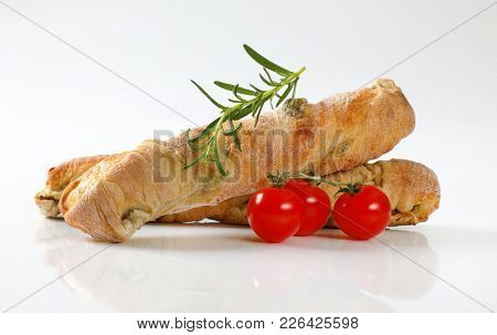 two loaves of olive ciabatta bread, rosemary and cherry tomatoes on white background