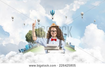 Beautiful Woman Writer In Hat And Eyeglasses Using Typing Machine And Pointing Upside While Sitting