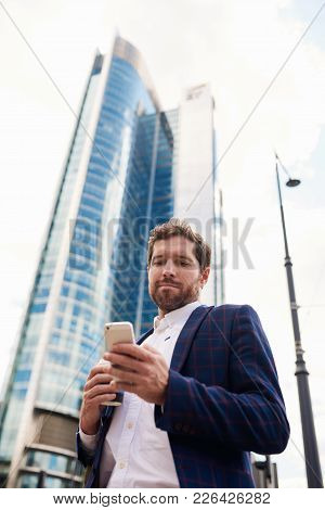 Young Businessman Standing In The City Drinking A Coffee And Reading A Text Message On A Cellphone W