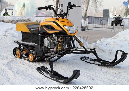 Perm, Russia - February 10, 2018: Yellow Snowmobile Stands Near The Ice Town On The Street Of The Ci