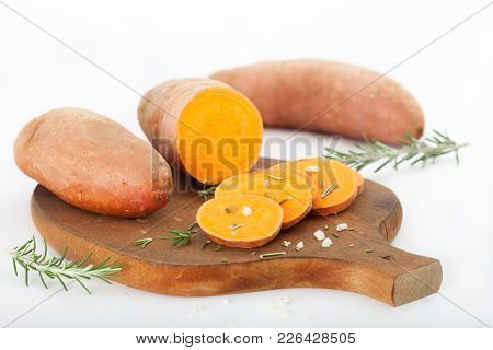Raw Sliced Sweet Potatoes On Wooden Table