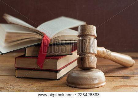 Judges Old Gavel Closeup, Books On Law In The Background. Wooden Table