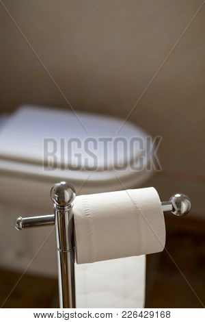 closeup of a roll of toilet paper in a roll holder in front of a toilet with its seat down in a beige restroom, with some blank space on top