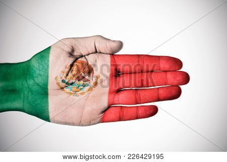 the palm of a young caucasian man patterned with the flag of Mexico, against a-white background with a slight vignette added