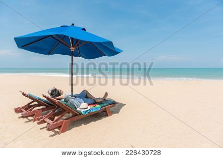 Young Asian Man Traveler Lying On Beach Bench With Blue Umbrella Overhead. Surrounded By Beautiful T