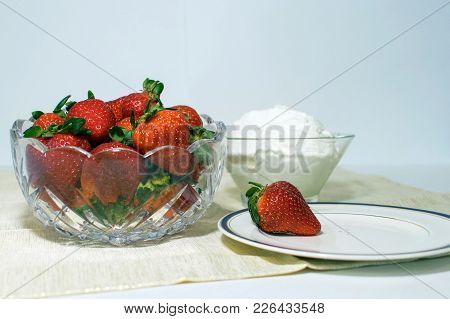 A Glass Bowl Filled With Strawberries And Beside That Is A Bowl Of Whipped Cream Also A Plate With O