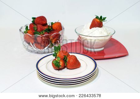 Strawberries Fil A Bowl, On Top Of Whipped Cream And A Stack Of Plates.