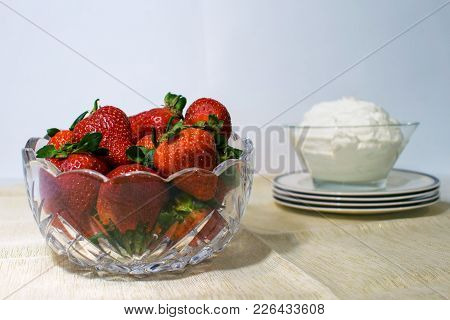 A Glass Bowl Filled With Strawberries And Another Bowl To The Side Filled With Whipped Cream.