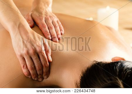 Close Up Macro Detail Of Hands Massaging Female Upper Back And Shoulder In Spa. Ambient Candlelight