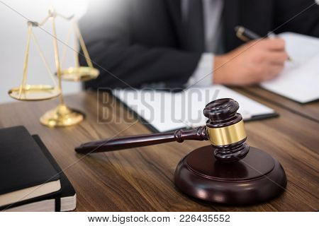 Lawyer Hand Writes The Document In Court (justice, Law) With Sounding Block And Golden Weight.