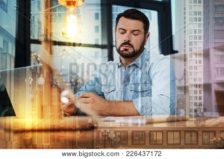 Unusual Idea. Calm Curious Thoughtful Man Looking Attentively At The Documents On The Table While Si