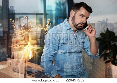 Troubles At Work. Professional Handsome Man Talking On Phone While Dealing With His Tasks