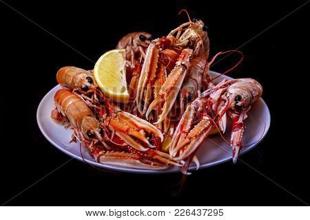Cooked Langoustine With Lemon On A Black Background